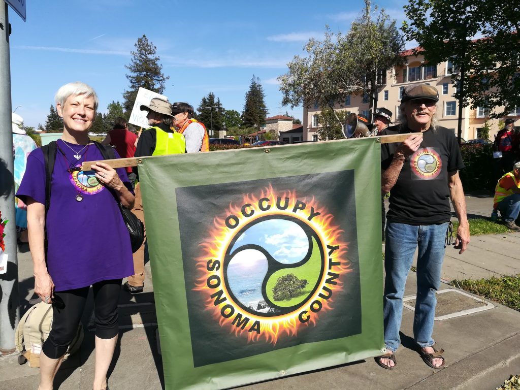 Occupy Sonoma County members carry the banner on with the new OSC logo on May Day, 2018
